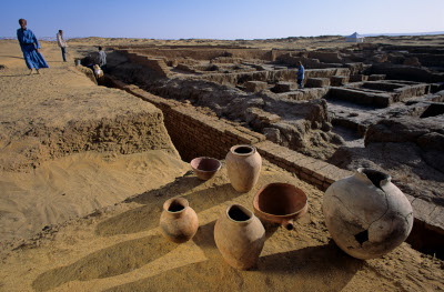 image of several old, damaged earthenware vases sitting on a ledge overlooking an area of dug out excavation