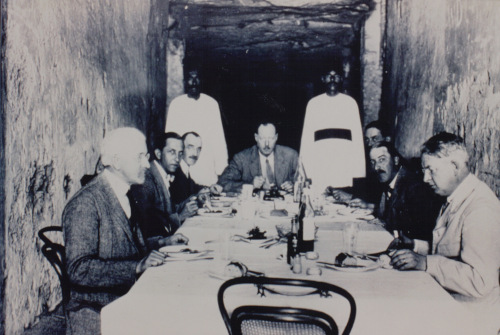 black and white photograph of James Poitrine, Harry Burton, Alfred Lucas, Arthur Callender, Arthur Mace, Howard Carter and Alan Gardiner lunching in the Valley of the Kings